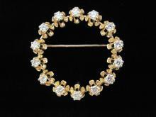 A diamond and fourteen karat gold circle brooch,