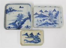 Three Japanese blue and white glazed rectangular porcelain trays depciting landscape scenes, 19th century