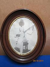 OVAL DEEP WALNUT FRAME 12 X 11 WITH ETHNIC MAN ON A BANJO