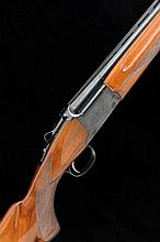 WINCHESTER A 12-BORE SINGLE TRIGGER OVER AND UNDER GUN, NO. K421759 28-inch monobloc barrels with 2 3/4-inch chambers, about 1/4 and 3/4 choke borings, machined ventilated rib, the frame with scroll engraving, selective single trigger, 14-inch