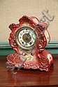 WATERBURY CHINA MANTLE CLOCK. Eight day time/strike with brass works and porcelain dial. Rose colored case has floral decoration and...