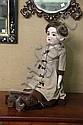 BISQUE HEAD DOLL. Brown sleep eyes and an open mouth. Marked on the back under the wig,