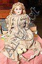 BISQUE HEAD DOLL. Unmarked with brown glass eyes and an open mouth. Wearing a period silk dress. 26