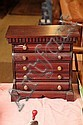 MINIATURE CHEST OF DRAWERS. Mahogany having a dentil carved cornice, five rolled drawers with brass pulls, a side door and shaped ap...