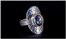 Northern Lights Mystic Topaz Ring, bezel set 2.5ct topaz, with an exotic mix of purple and green with blue flashes, mounted on a hand planished shield of silver with a four ridged shank; size Q