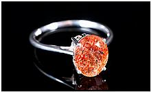 Tanzanian Sunstone Solitaire Ring, an oval cut of the peach and burnt orange feldspar, mined in Tanzania, measuring 2cts, set on a narrow, tapering silver shank; size Q
