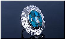 Mojave Turquoise Ring, an oval cut cabochon of the turquoise, mined in the Mojave Desert, USA, 7.75cts bezel set in a planished silver curved oval, mounted on a generous silver band shank