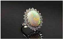 18ct White Gold Opal and Diamond Cluster Ring. The Large Opal Surrounded by 20 Small Diamonds, Diamond Weight Approx 1.5 cts. Fully Hallmarked For London 1974.