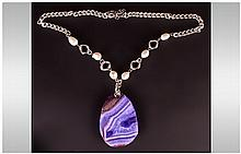 Large Purple Banded Agate Pendant Necklace, the spectacular agate pendant of approximately 90cts, with a white  Austrian crystal set bale, suspended from a white fresh water baroque pearl and silvered chain necklace; 22 inches long