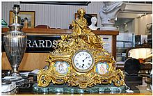 French Gilt Brass Figural Mantle Clock. Central Dial Between two Sevres Style Plaques. Raised on a Green Marble Base.