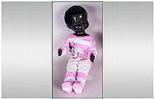 Pedigree Black Doll, black plastic body with moveable limbs and  glass eyes. Dressed in pyjamas. c 1