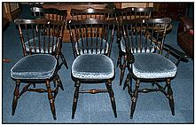 A Set of Dark Stained Spindle Back Chairs with shaped backs. Consisting of 4 stand chairs and two ca