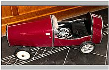 A Replica Childs Pedal Racing Car of the 1930's Style, painted in maroon red, open top. Similar to a