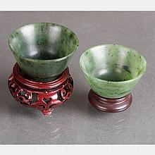 Two Chinese Carved Spinach Jade Cups on Carved Hardwood Stands.