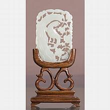 A Chinese Carved White Jade Pendant on a Carved Rosewood Stand.