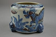 A Chinese Blue & White Porcelain Brush Washer The blue & white porcelain brush washer with red underglaze accents, depicting a pair of opposing dragons in a landscape setting, and having three applied figural feet.Size: 3
