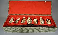 A Set of Seven Japanese Carved Bone Figures 20th centuryThe carved, scrimshawed bone figures with polychromed accents throughout, depicting the Immortals, and raised on the accompanying large carved, wire inlaid wood stand. Size: 6