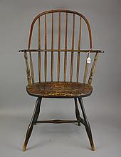 An 18th Century Sack Back Windsor Arm Chair American, New England, having seven spindles above the saddle seat, over the splayed legs joined by an H-form stretcher.Size: 40 1/4
