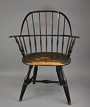 An 18th Century Sack Back Windsor Arm Chair American, New England, having seven spindles above the oval seat, over the splayed legs joined by an H-form stretcher.Size: 36