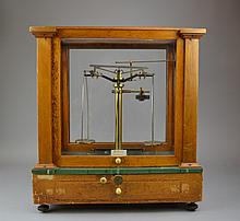 A Dutch Cased Pharmacy Scale Becker's Sons, Rotterdam, the instrument housed within an oak and glass case with sliding front access panel, and raised on four feet.Size: 18 1/4
