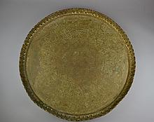 A Middle Eastern Brass Tray Having a scalloped rim and incised decoration depicting Egyptian motifs and scenes throughout.Size: 26 1/4
