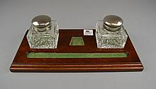 An Antique Wood and Glass Ink Stand Of rectangular form, centering a pen tray and additional receptacle, and having two cut glass ink wells with hinged silvered metal covers.Size: 11 3/4