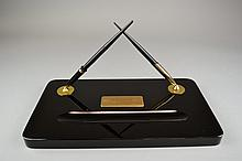 A Sheaffer Black Onyx Ink Stand Circa 1937Of rectangular form, centering a pen tray beneath an etched brass presentation placard, marked Sheaffer's to reverse, together with two associated fountain pens.Size: 14