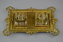 An Antique Brass Ink Stand Of rectangular form, each corner with pierced scrollwork, the whole raised on four feet and centering two associated glass ink wells.Size: 11 3/4