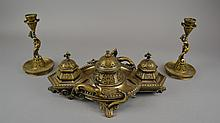 An Antique Three Piece Brass Desk Set The ink stand of tripartite form, centering a covered well and decorated throughout with scrolling naturalistic motifs in the Aesthetic style, flanked to each side by applied mythical and raised on four feet,