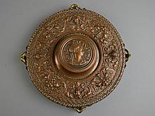 An Antique Brass Ink Well Of circular form, the raised central well having a repousse portrait medallion cover within a scrolling foliate, flowering urn, and mask surround, and raised on four figural dolphin feet.Size: 2 1/4