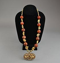 An Agate and Carved Bone Necklace Having figural carved bone elephant-form beads set between by agate beads, suspending the silvered metal-set carved bone pendant depicting a pair of opposing elephants.Size: 24