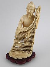 A Japanese ivory figure of a fisherman displaying