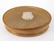 An oval pale horn box with silver cartouche on
