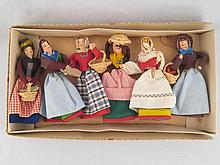 Six egg cosies in the form of miniature dolls, all