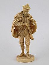 A carved ivory figure of traveller with tattered
