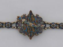 A Russian silver-gilt and cloisonné enamel lady's belt, maker's mark AD (Cyrillic), St. Petersburg, circa 1890, in traditional colours, the buckle with champlevé enamel kindjal clasp, 70 cm. long