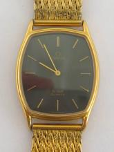 OMEGA de Ville, a gilt metal mid-size quartz wristwatch, no. 1365, the tonneau shaped case with dark grey metallic dial and applied baton detail, the case 27mm wide, on a woven gilt metal strap to an Omega fold over clasp, together with Guarantee booklet (1984)