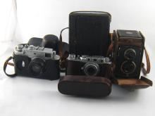 Four cameras, being a Rolleicord in ER case, a Soviet 35mm. FED in ER case, a Soviet Zorki-4 in ER case and an Eastman Kodak Premo 1/4 plate .