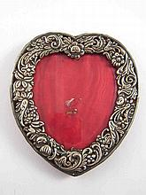 A late Victorian silver faced heart shaped photo frame with bevelled glass,