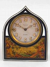 A strut back boudoir clock, the gilt gothic arch frame with black and white