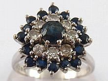 An 18 carat white gold sapphire and diamond cluster ring, size O, 5.9 gms.