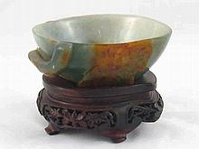 A Chinese jade bowl carved as a hollowed peach on a branch with a bat. 13x1