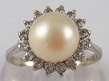 A white metal (tests 18 carat gold) clear stone and cultured pearl ring, pe