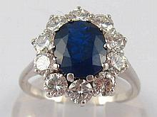 A white metal (tests 18 carat gold) sapphire and diamond ring, the round br
