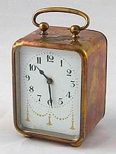 A brass cased bedside alarm clock, circa 1920, with gilt decorated enamel d