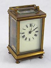 A brass carriage clock with white enamel dial and French movement.