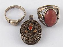 A mixed lot comprising two white metal rings and a locket.