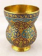 A hand wrought brass cup with champleve enamel