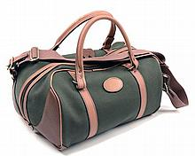 AN UNUSED GREEN CANVAS AND LEATHER HOLD-ALL BAG,