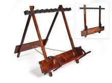 A TEAK PORTABLE FOLDING GUN RACK WITH LEATHER LINING AND BRASS MOUNTS,